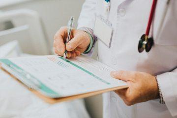 Lekarz ortopeda wypisujący dane w karcie pacjenta